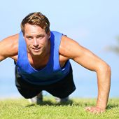 Push ups - fitness man exercising push up outside in grass in summer. Fit male athlete working out c