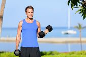 Fitness bicep curl - weight training man outdoors working out arms lifting dumbbells doing biceps cu