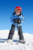 Young boy on skis, leaning on his poles, ready to hit the slopes