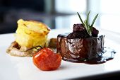 Roasted beef tenderloin with herb-potato muffin, mushroom ragout, baked tomatoes and rosemary-curran