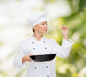cooking and food concept - smiling female chef, cook or baker with pan and spoon tasting food