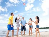 summer, holidays, vacation, happy people concept - group of friends having fun on the beach