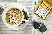 stock photo of cigarette lighter  - Cup of coffee lighter and cigarettes arranged on a newspaper