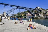 Porto, Portugal - July 27, 2013: The typical local children of the Ribeira District sunbathing after