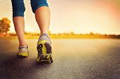picture of shoe  - an athletic pair of legs on pavement during sunrise or sunset  - JPG