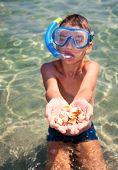 Boy wearing snorkeling gear showing seashells