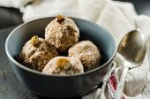 Energy balls in bowl with spoon and napkin on table