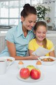 Happy mother and daughter reading greeting card at breakfast table