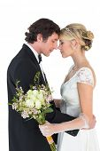 Side view of romantic newlywed couple standing head to head on white background
