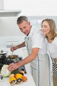 Side view of a happy couple preparing food in the kitchen at home