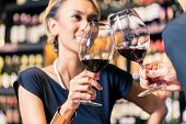 Close up of Asian couple clinking glasses in wine shop