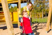 Family with Mother and daughter swinging and playing on play area or court