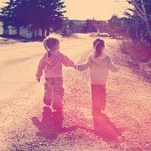 stock photo of walking away  - Two girls holding hands walking on road  - JPG