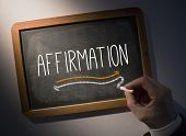 Hand writing the word affirmation on black chalkboard