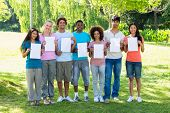 Group portrait of college students holding blank papers on campus