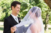 Happy young groom unveiling his bride in garden
