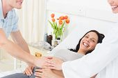 Portrait of happy pregnant woman with man and doctor in hospital ward