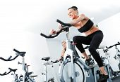 Young athletic female spinning veloargometers in gym, male behind