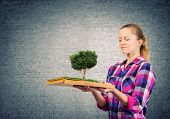 Young woman in casual holding opened book with green tree