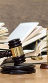 Wooden gavel, golden scales of justice and books on wood background