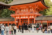KYOTO, JAPAN - APRIL 20th : group of people in shimogamo-jinja orange archway take a ceremonial phot