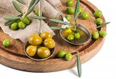picture of marinade  - Marinaded and raw olives olive oil on a wooden kitchen board - JPG