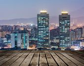 Colorful city night scene with modern skyscrapers, Taipei, Taiwan. Focus on wooden floor.