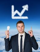 Businessman holding light bulb and pointing against blue sky over clouds at high altitude