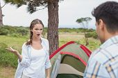 Young couple with tent standing on countryside landscape