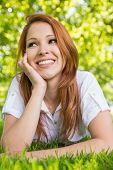 Pretty redhead relaxing in the park on a sunny day