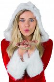 Pretty girl in santa outfit blowing on white background