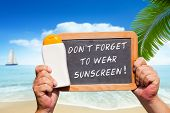 stock photo of slating  - Human Hands hold a bottle sunscreen and a slate blackboard with text message  - JPG