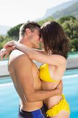 Side view of a romantic young couple by swimming pool on a sunny day