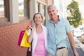 Happy mature couple walking with their shopping purchases on a sunny day