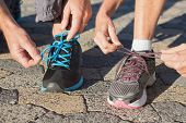 Couple tying their laces of running shoes on a sunny day