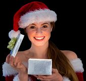 Pretty redhead in santa outfit opening a gift smiling at camera on black background