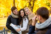 travel, people, tourism, photography and friendship concept - group of smiling friends with map taki