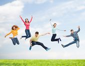 happiness, freedom, friendship, summer and people concept - group of smiling teenagers in air over n