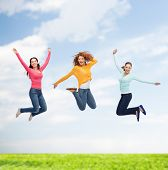 happiness, freedom, friendship, summer and people concept - group of smiling young women jumping in