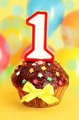 Birthday cupcake with chocolate frosting on bright background
