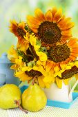 Beautiful sunflowers in pitcher with pears on table on bright background