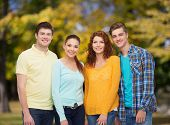 friendship, summer vacation, nature and people concept - group of smiling teenagers standing over gr