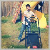 Little boy using the lawn mower