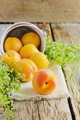 stock photo of apricot  - ripe apricots scattered on the old wooden background - JPG
