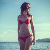 Outdoor summer outdoor portrait of young pretty woman girl standing in red bikini swimsuit