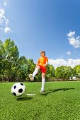 Boy kicking football with one leg