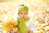 stock photo of knitting  - Autumn Baby Portrait In Fall Yellow Leaves Little Child In Woolen Hat Beautiful Kid in Park Outdoor Knitted Clothing for October Season - JPG