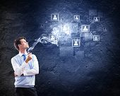 Young handsome businessman smoking pipe with business items at background
