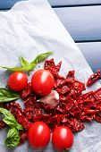Sun dried and fresh tomatoes, basil leaves, garlic on color wooden background