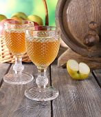 Still life with tasty apple cider and fresh apples, on nature background